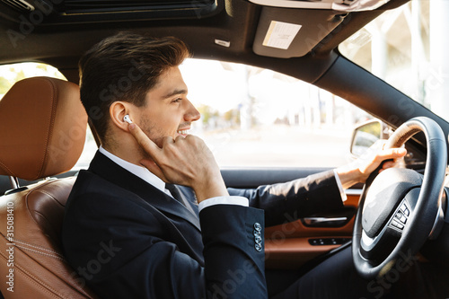 Cuadros en Lienzo Image of young businesslike man in suit using earbuds while driving car
