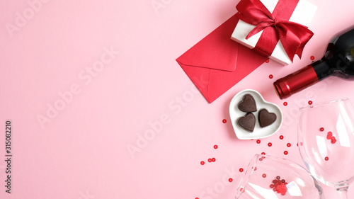 Valentine's day background with wine bottle, gift box, glasses, heart shaped candies, red paper envelope and confetti on pink background Wallpaper Mural