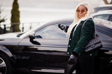 Chic African American Blond Woman In Black Leather Clothes Posed Against Race Modern Car With Key In Hand.