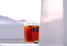 A Transparent Glass Mug Of Black Tea On White Windowsill On Sky Background. Morning. Breakfast.
