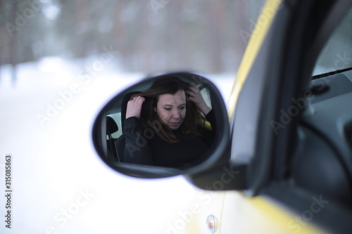 Photo Beautiful young woman with green eyes and red hair in a yellow car in a winter s