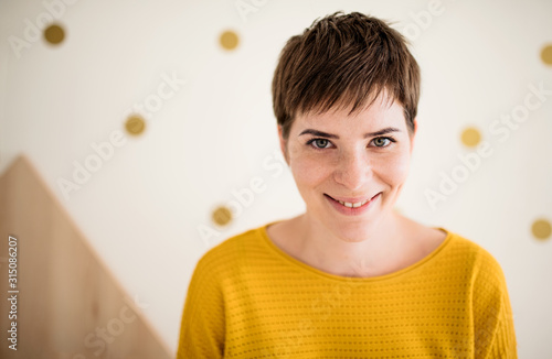 Obraz Front view of young woman standing indoors at home, close-up. - fototapety do salonu