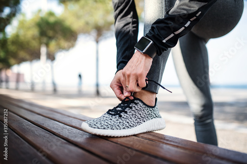 Photographie A young sportswoman with smartwatch outdoors in city, tying shoelaces