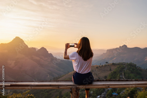 Obraz Young woman traveler taking photo with smart phone at sunset over the mountain - fototapety do salonu