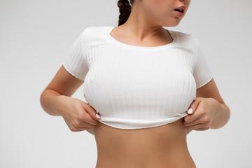 Crop sensual young lady taking off shirt