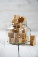 Brown Sugar Cubes In Glass Jar On Light Background