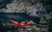 Couple Sitting In Red Hammock ...
