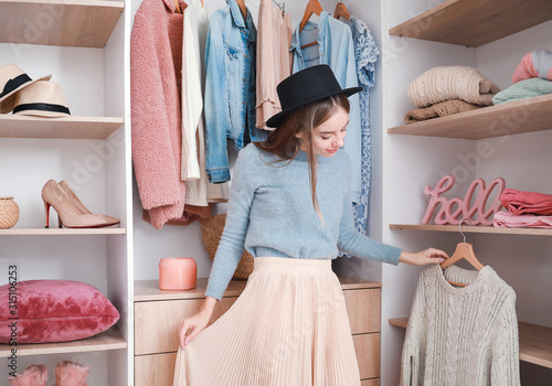 Photo Beautiful young woman choosing clothes from large wardrobe