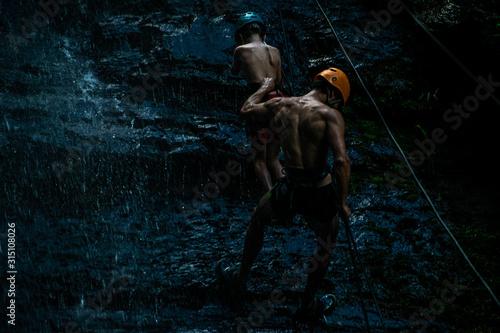 Photo Rappel, hombre descendiendo por montaña con niño.