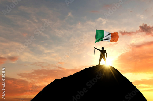 Fotomural Irish flag being waved at the top of a mountain summit