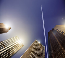 Airplane Vapor Trail In Blue Sky Above Highrise Buildings, Travel Concept