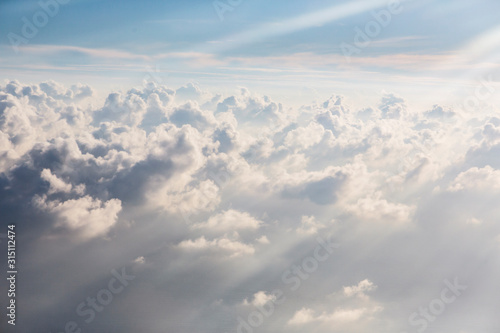 Aerial view sunbeams over fluffy white clouds - 315112474