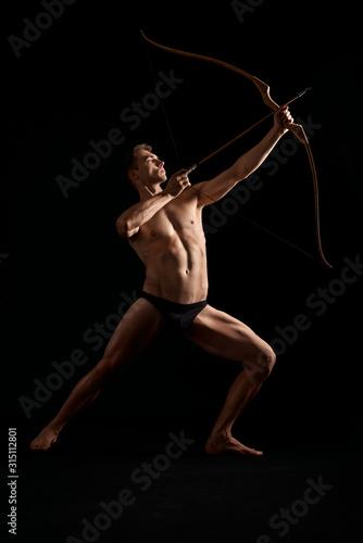 Athletic archer shooting with bow. Canvas Print