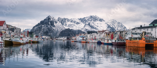 Panoramic view of Henningsvaer, cozy fishing village in Lofoten Islands, Northern Norway. Scenic landscape with mountains, houses, boats, sky and reflection in the water, outdoor travel background