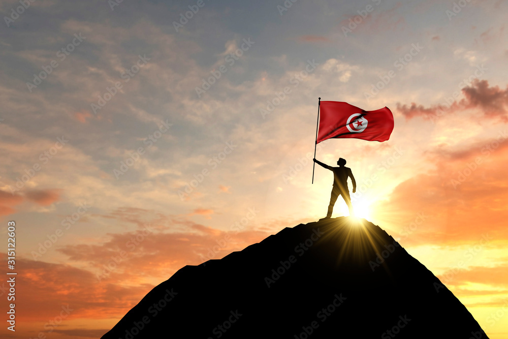 Fototapeta Tunisia flag being waved at the top of a mountain summit. 3D Rendering