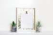 Lifestyle home decoration with frame and place for text. Marbled geometric succulent planters with beautiful tiny succulent plants on white shelf against white wall.