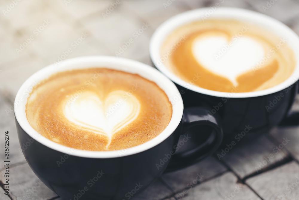 Fototapeta Two black mugs with a coffee drawn in a heart shape.