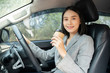 Asian female driver smiling and drinking coffee in the car, Beautiful girl holding an eco paper coffee cup,looking to camera while driving her car, happy life transport in city