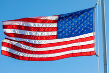 American Flag, Backlit By The Setting Sun, Waving In The Wind.