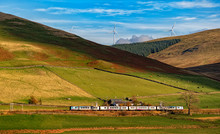 Beautiful Landscape ,train A Pair Of Scotrail Passenger Trains Climbon Scottish Highlands Scenery Of Mountains And Wind Turbine On A Summer's Day