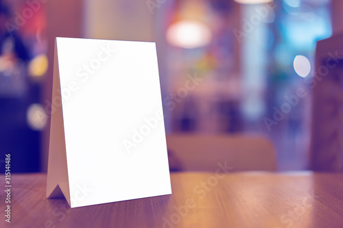 Obraz Mock up Label the blank menu frame in Bar restaurant ,Stand for booklets with white sheets paper acrylic tent card on wooden table cafeteria blurred background can inserting the text of the customer. - fototapety do salonu