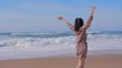 Woman walking with arms up on beach, summer travel concept