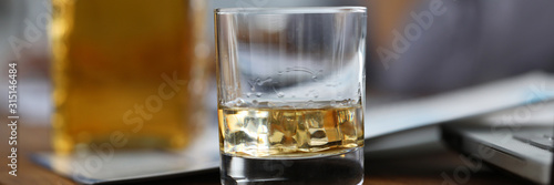 Valokuva Focus on glassful with alcoholic beverage with ice-cube on wooden brown table