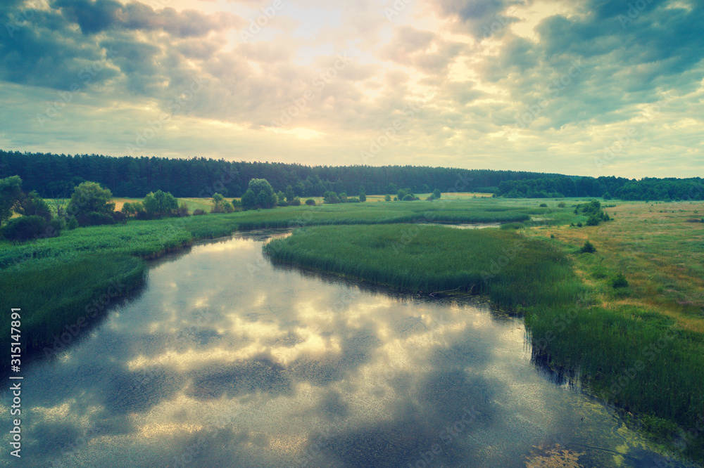 Fototapeta Aerial view of countryside and brook in evening at sunset light. Beautiful nature landscape