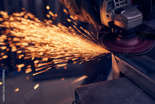 Fototapeta Worker cutting metal with grinder. Sparks while grinding iron obraz
