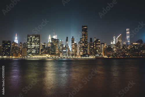 Fototapety, obrazy: Manhattan Skyline in New York City in the Heart of America during Night Time with Reflection