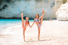 Adorable Active Little Girls At Beach During Summer Vacation