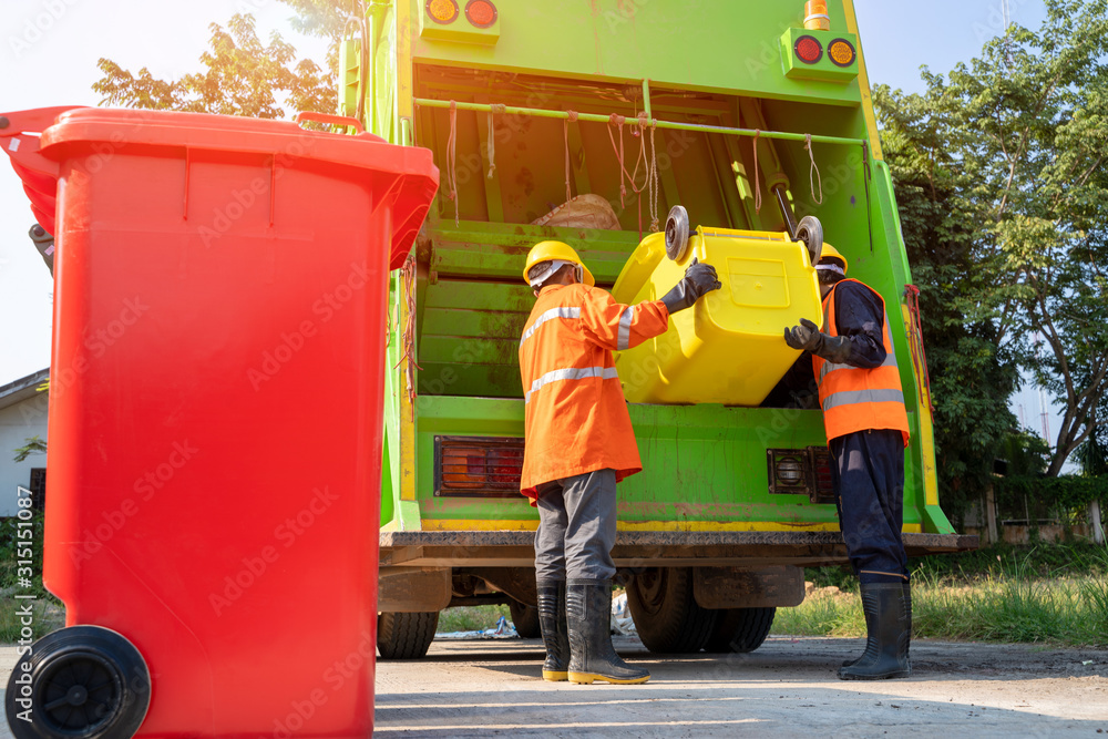 Fototapeta Two garbage men working together on emptying dustbins for trash removal with truck loading waste and trash bin.