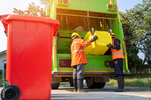 Photo Two garbage men working together on emptying dustbins for trash removal with truck loading waste and trash bin