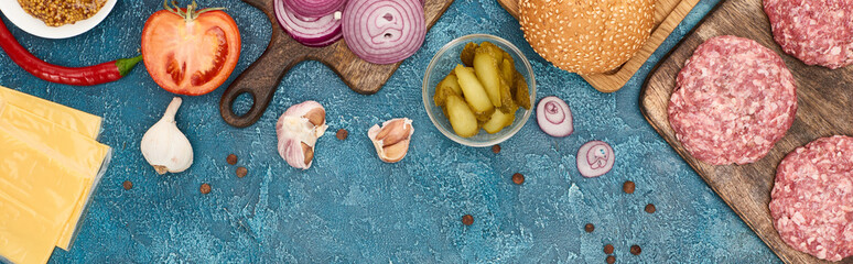 top view of fresh burger ingredients on blue textured surface, panoramic shot