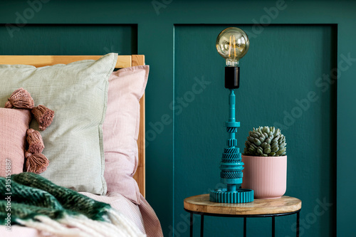 Obraz Stylish home interior of bedroom with design coffee table, table lamp, succulent and beautiful plant. Green wall panelling. Beautiful bed sheets, blanket and pillow. Template. Home staging.  - fototapety do salonu