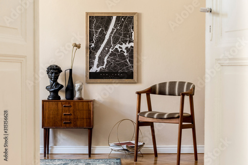 Fototapeta Modern composition of living room interior with brown mock up poster frame, design retro commode, vintage chair, flowers in vase and elegant accessories. Template. Stylish home staging. Japandi. obraz