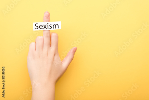 Fotomural  cropped view of man showing middle finger with card sexism isolated on yellow