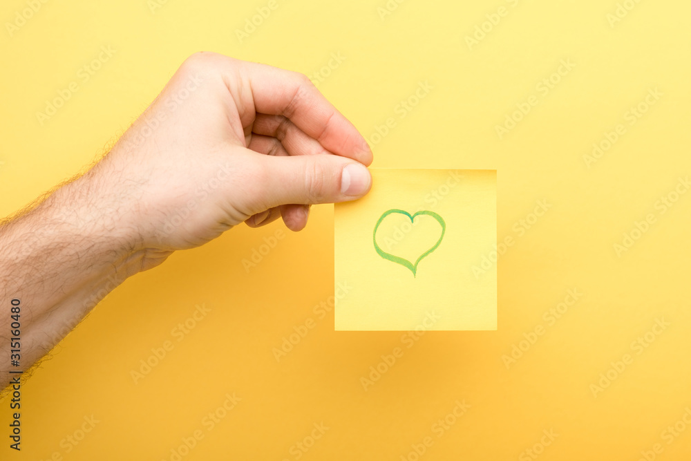 Fototapeta cropped view of man holding sticky note with heart on yellow background