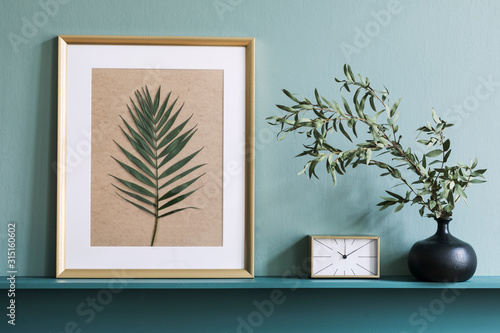 Obraz Stylish living room interior at elegant apartment with mock up poster frame, flowers in vase, gold clock and elegant accessories on the shelf. Green wood panelling. Modern home staging. Template.  - fototapety do salonu