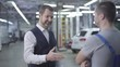 Portrait of adult bearded Caucasian man in elegant outfit taking car keys from auto mechanic and shaking his hand. Owner taking back fixed car from repair shop. Warranty service, car repair.