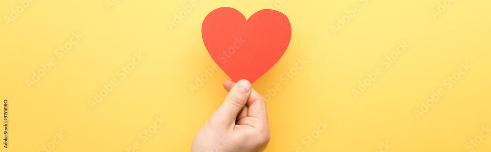 Fototapeta panoramic shot of man holding heart-shaped card isolated on yellow