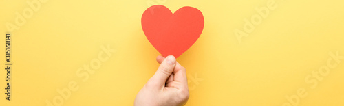 Obraz panoramic shot of man holding heart-shaped card isolated on yellow - fototapety do salonu