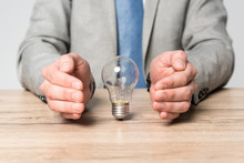Partial View Of Businessman Showing Protection Gesture Near Light Bulb Isolated On Grey