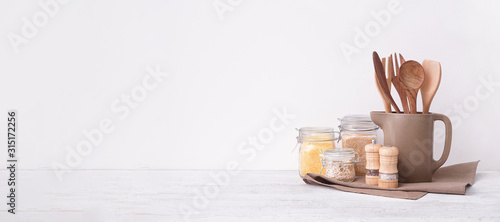 Set of kitchen utensils and groats on table near white wall with space for text Canvas Print