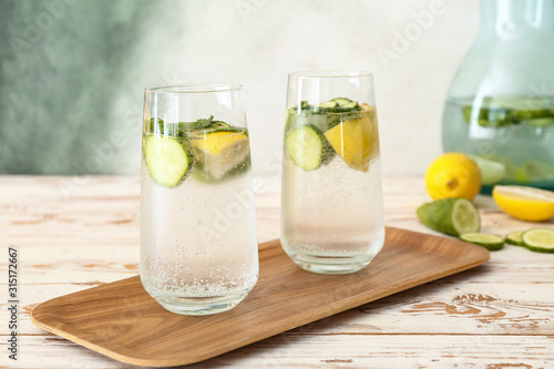 Obraz Glasses of cold cucumber water on white table - fototapety do salonu