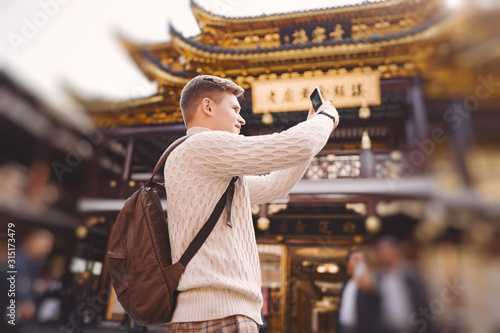male tourist taking photos of a pagoda at Yuyuan market in Shanghai during his v Wallpaper Mural