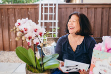 Happy Woman Holding Greeting Card While Sitting On Chair In Yard