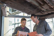 Mechanics with clipboards talking under car in auto repair shop