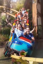 Portrait Enthusiastic Friends Cheering Riding Roller Coaster At Amusement Park