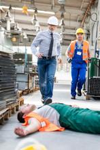 Workers Running Toward Fallen Coworker Unconscious On Factory Floor